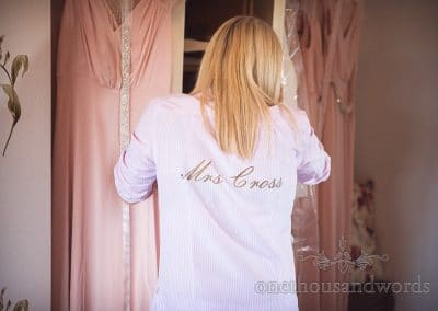 Bride in night shirt with married name embossed on back on wedding morning