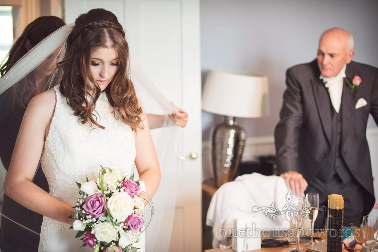 Bride in wedding dress is put into her veil on wedding morning under fathers watchful eye