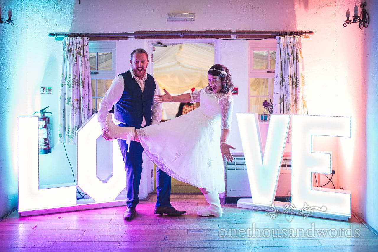 Bride in wellies poses with groom and love letters at Coppleridge Inn Wedding Photographs