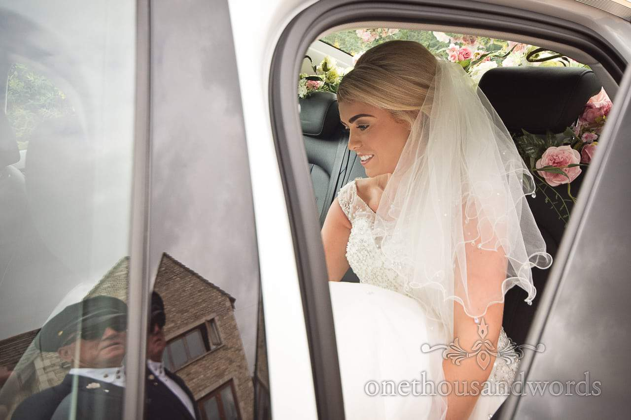 Bride in white dress and veil is helped into wedding car with flowers by chauffeur