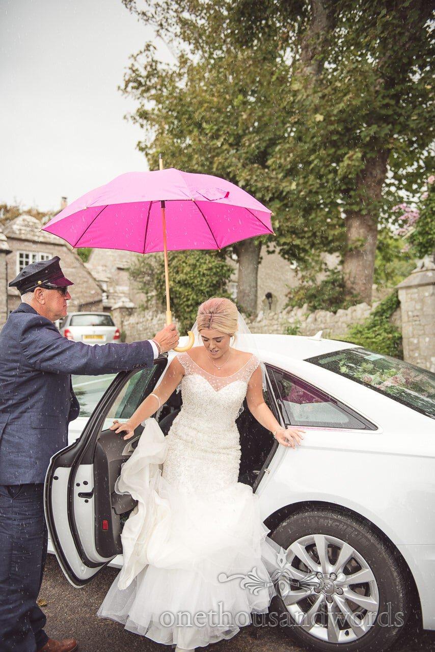 Bride in white wedding dress exits wedding car under pink umbrella in the rain