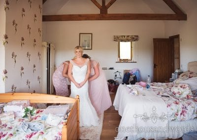 Bride is buttoned into white wedding dress at Purbeck Valley Farm on wedding morning