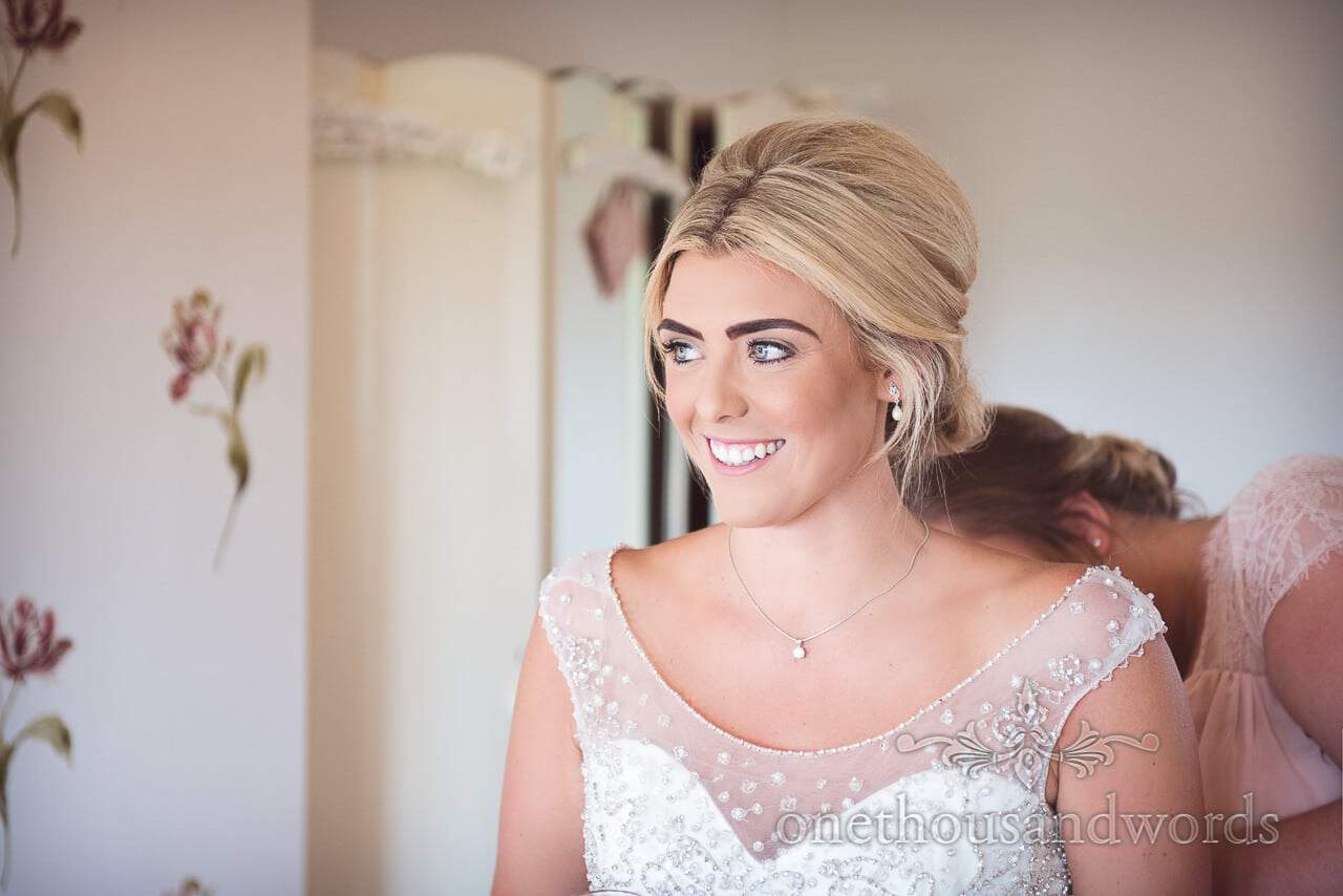 Bride looks out at sunny weather as she is buttoned into her wedding dress