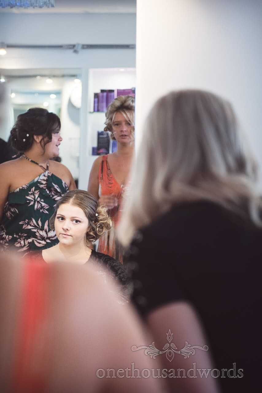 Bride's daughter examines her wedding hair style in mirror on wedding morning