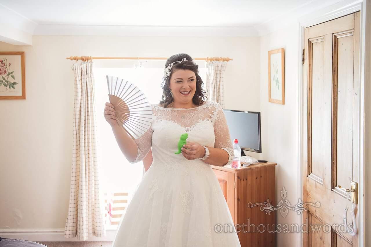 Bride with dinosaur fans herself before Coppleridge Inn Wedding