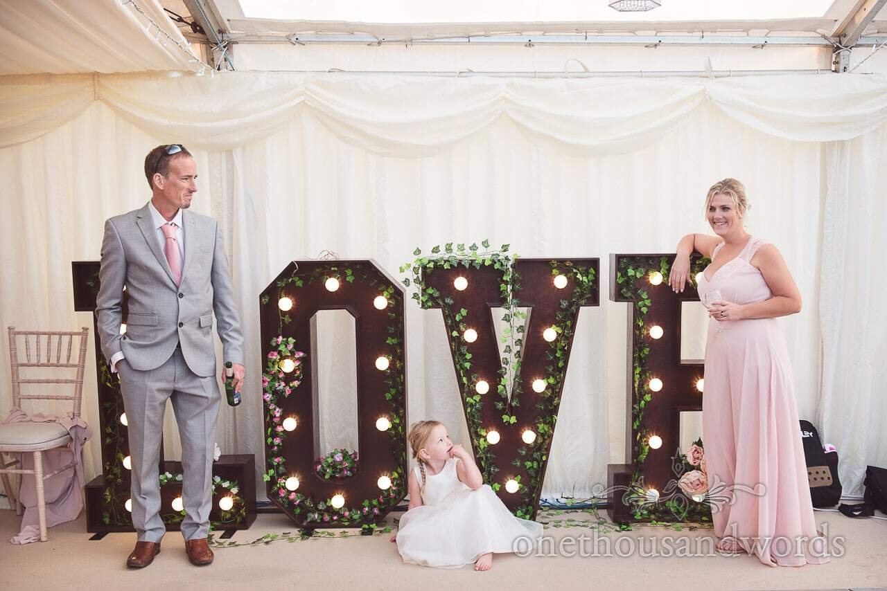 Bridesmaid and family pose with LOVE sign at Purbeck Valley Farm wedding photographs