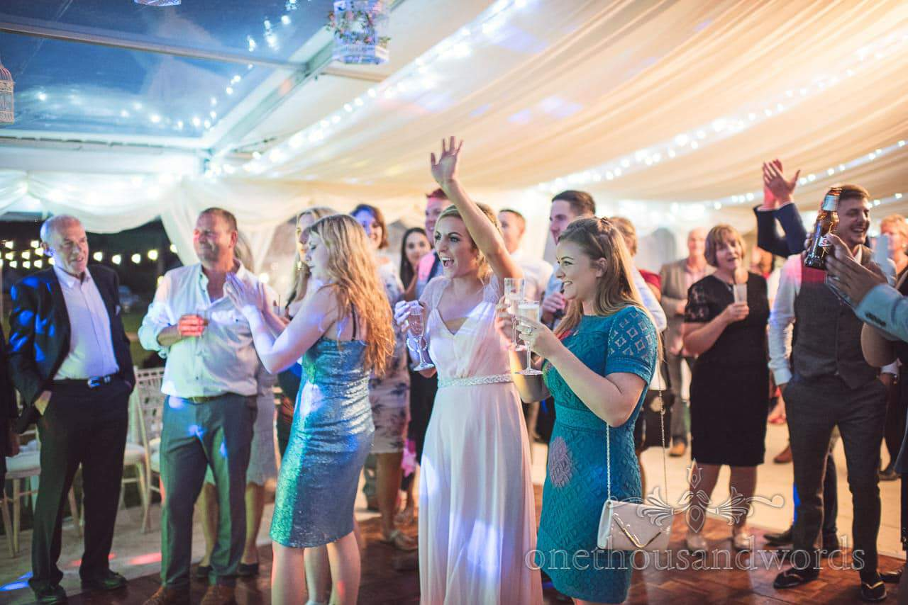 Bridesmaid and guest cheer during first dance at Purbeck Valley Farm wedding photographs