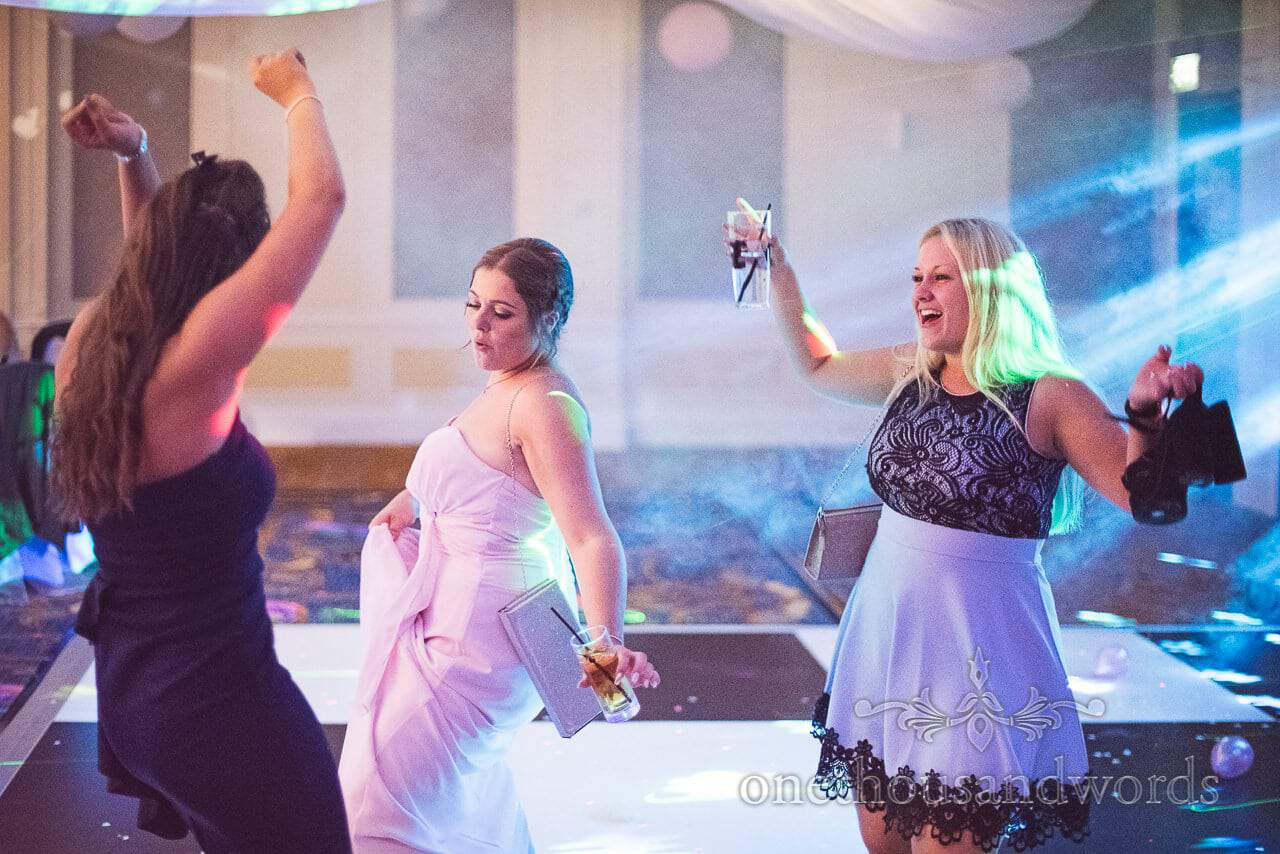 Bridesmaid and wedding guests throw shapes on wedding dance floor