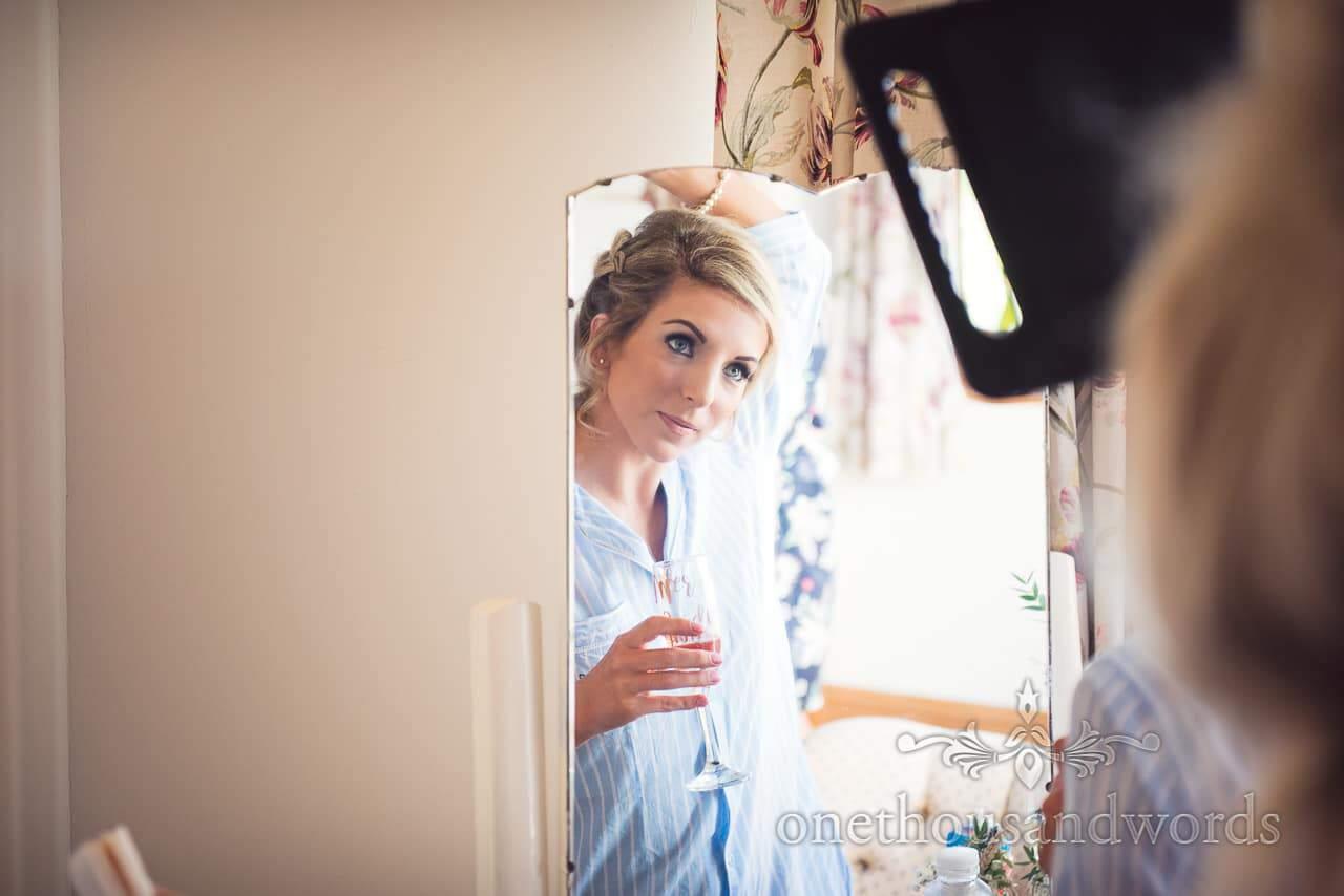 Bridesmaid checks wedding hair style in mirrors during bridal preparations