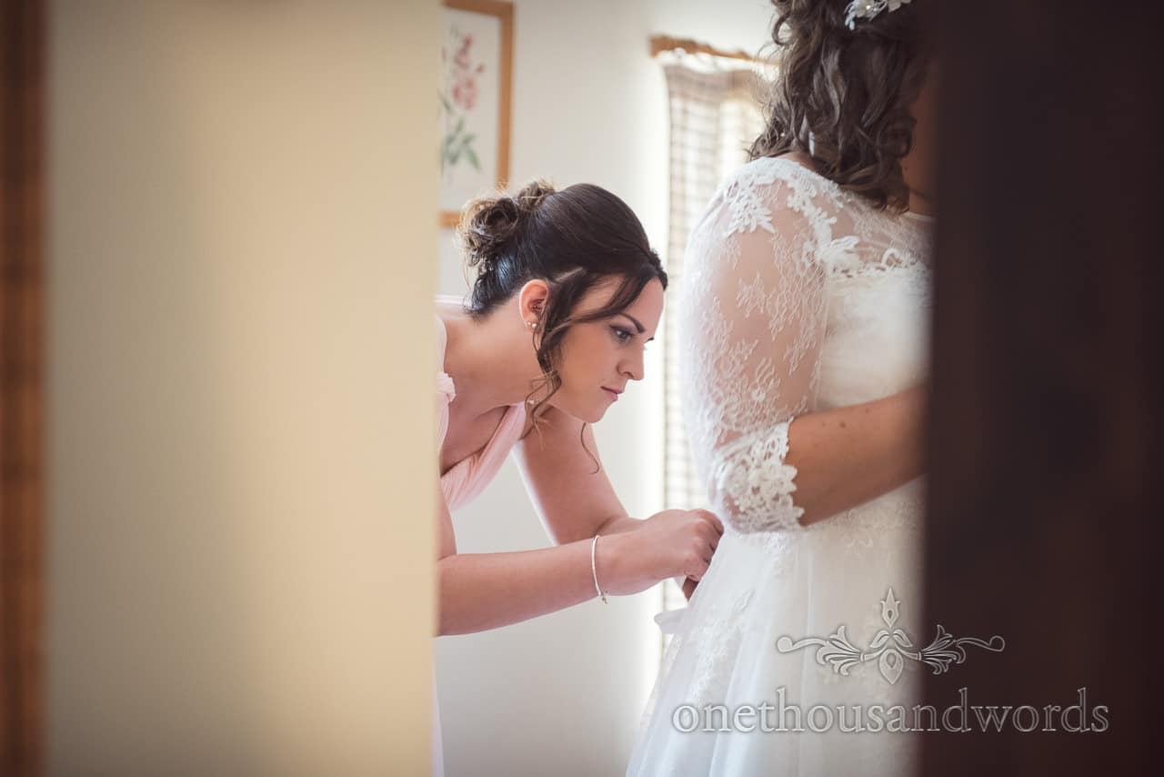 Bridesmaid helps bride with dress on morning of Coppleridge Inn Wedding