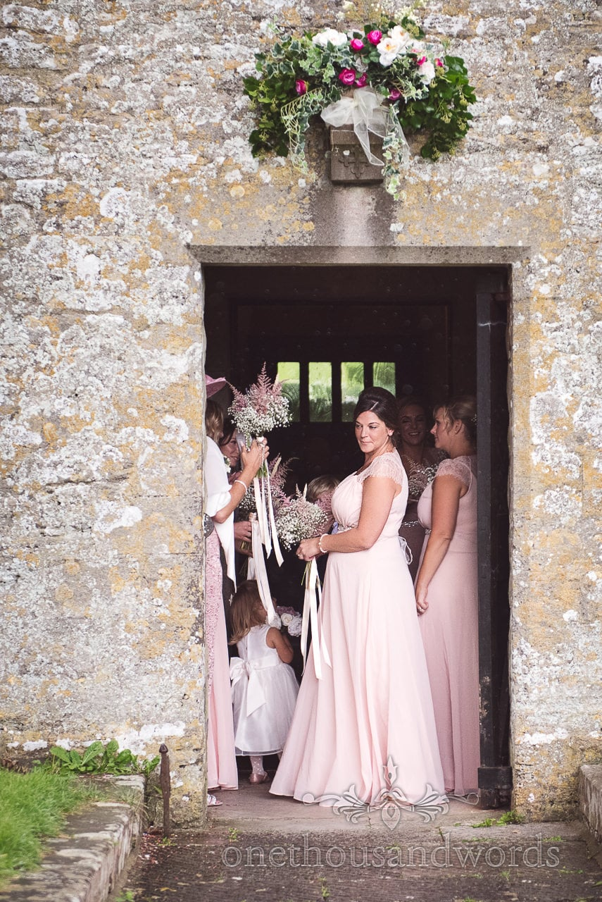 Bridesmaid in pink wedding dress under flower spray looks out of stone church at rain