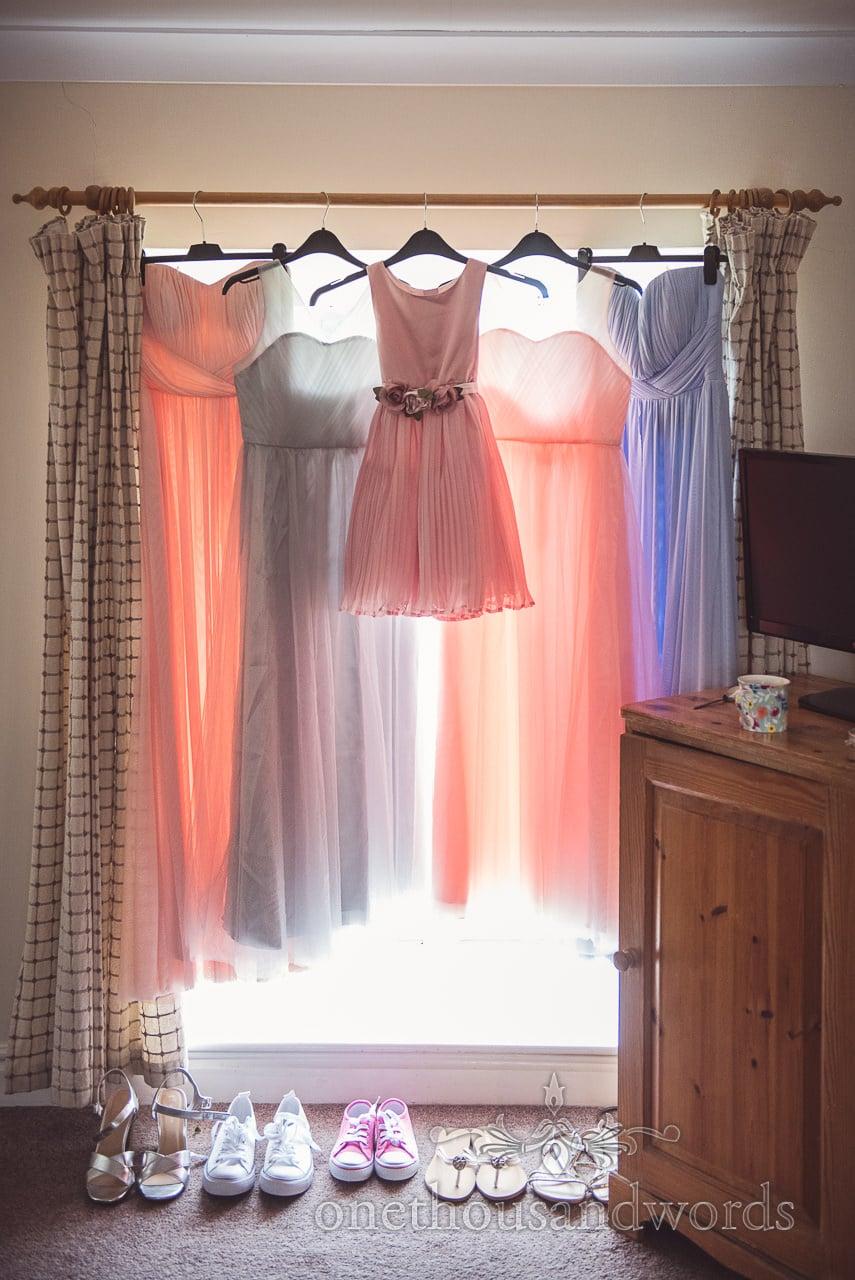 Bridesmaids and flower girl dresses hang in window at Coppleridge Inn Wedding Photographs