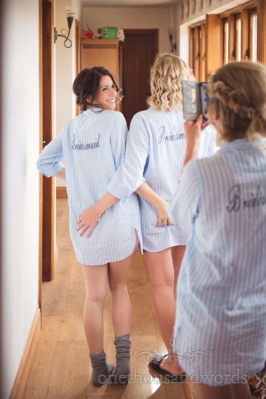 Bridesmaids in matching night shirts grab each others bottoms on wedding morning