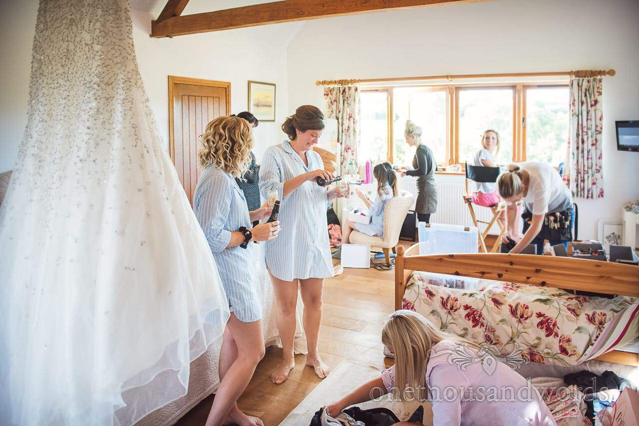 Bridesmaids in matching nights shirts pour champagne during wedding morning preparations