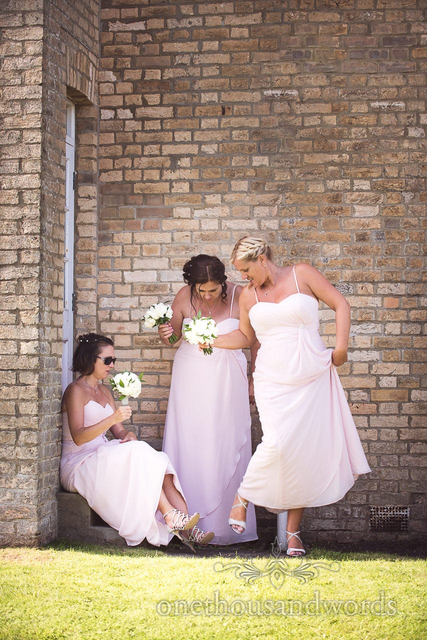 Bridesmaids in pink dresses shelter from sun next to brick wall and compare wedding shoes