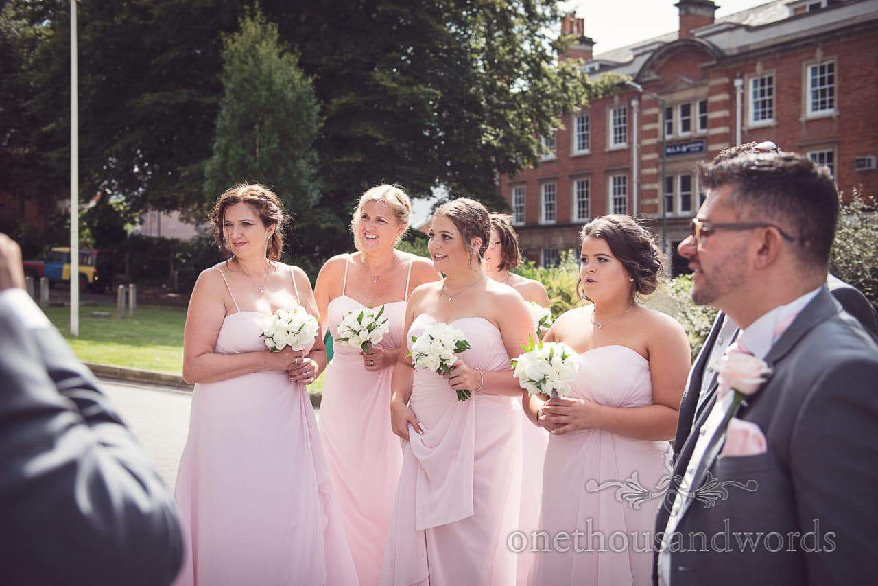 Bridesmaids in pink dresses with white rose bouquets outside Bournemouth church