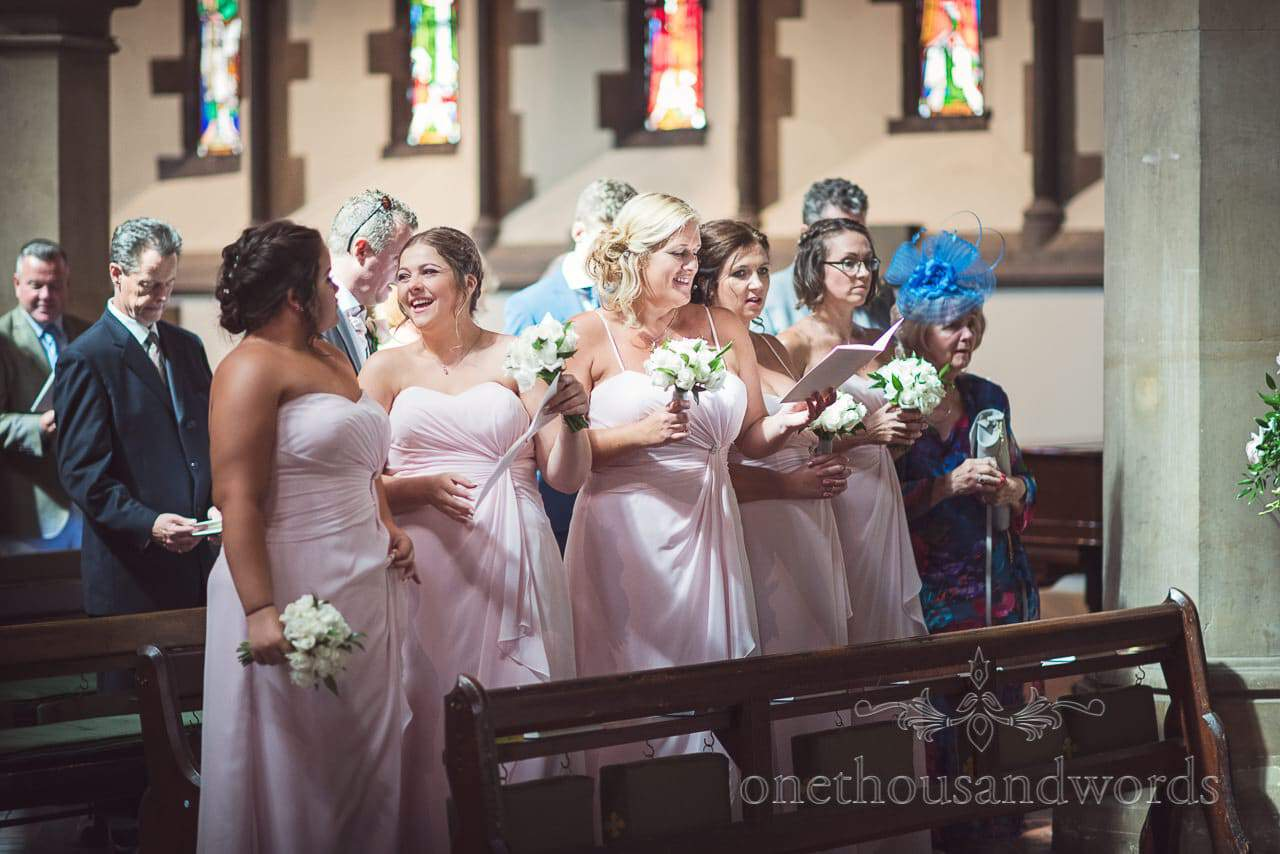 bridesmaids in pink laughing during wedding service at St Peter's Church Bournemouth