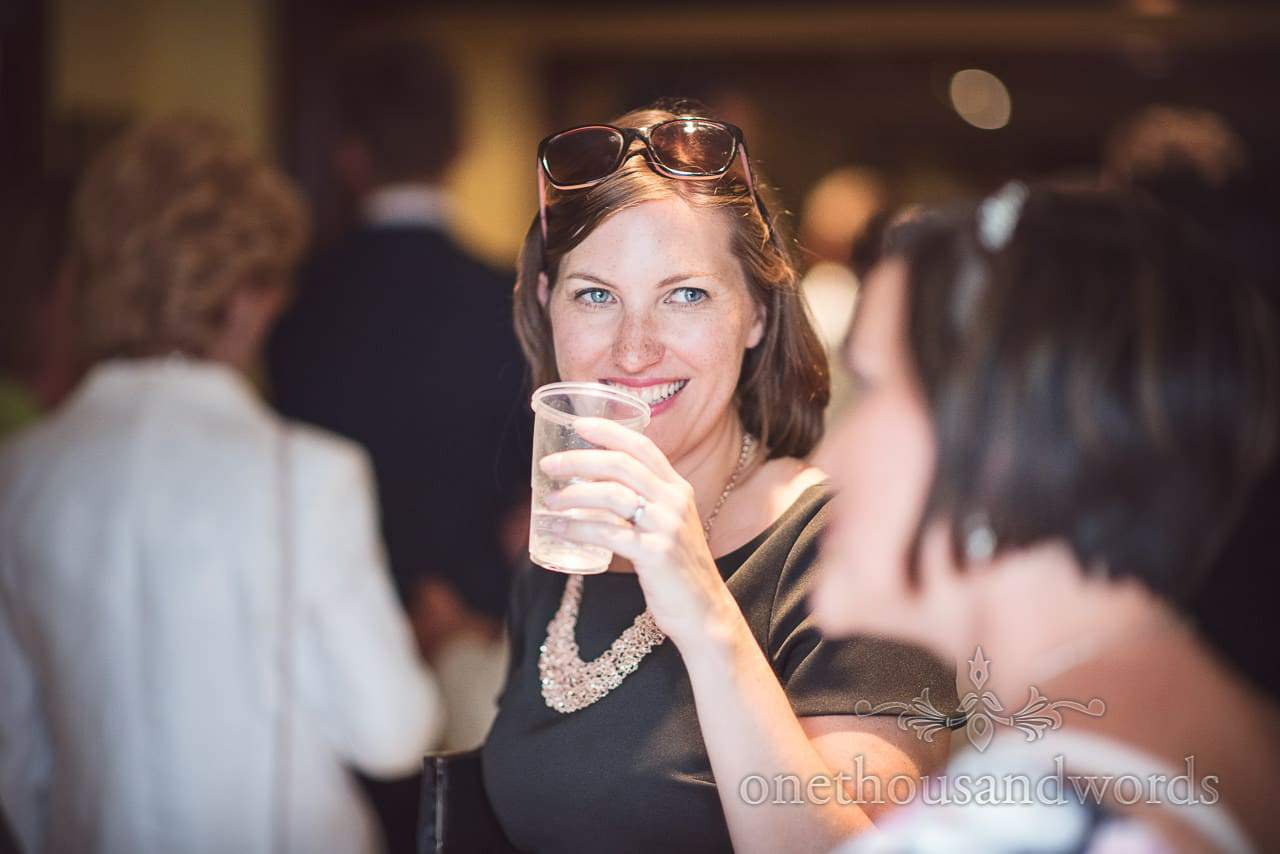 Brunette wedding guest with freckles and sunglasses on head drinks during wedding line up