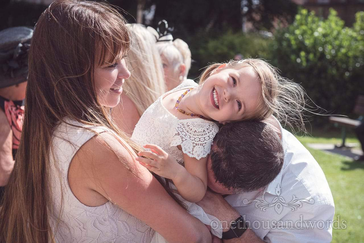 Child wedding guest is tickled by parents outside Bournemouth Church wedding