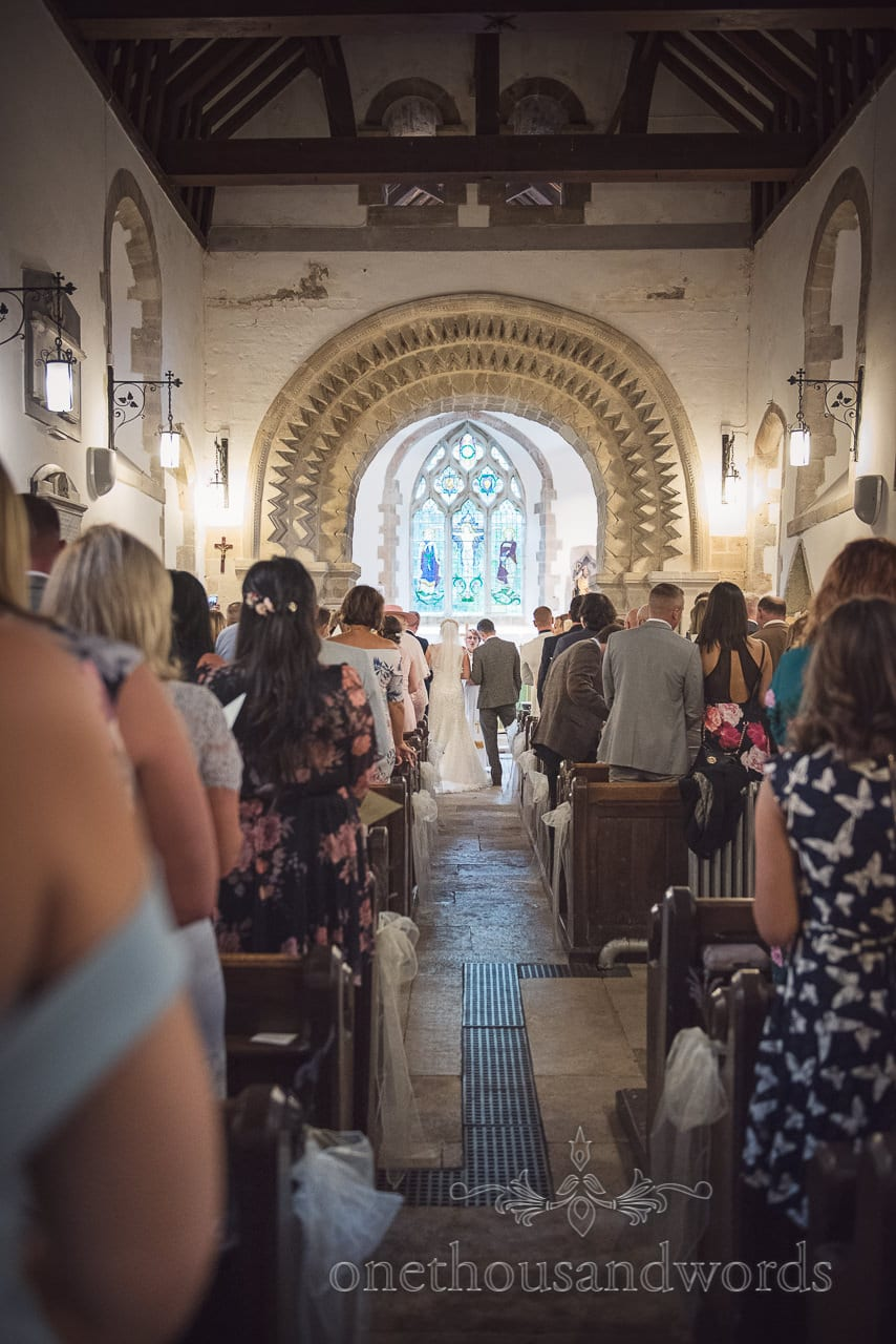 Church wedding ceremony under amazing carved stone archway in Worth Martravers Church