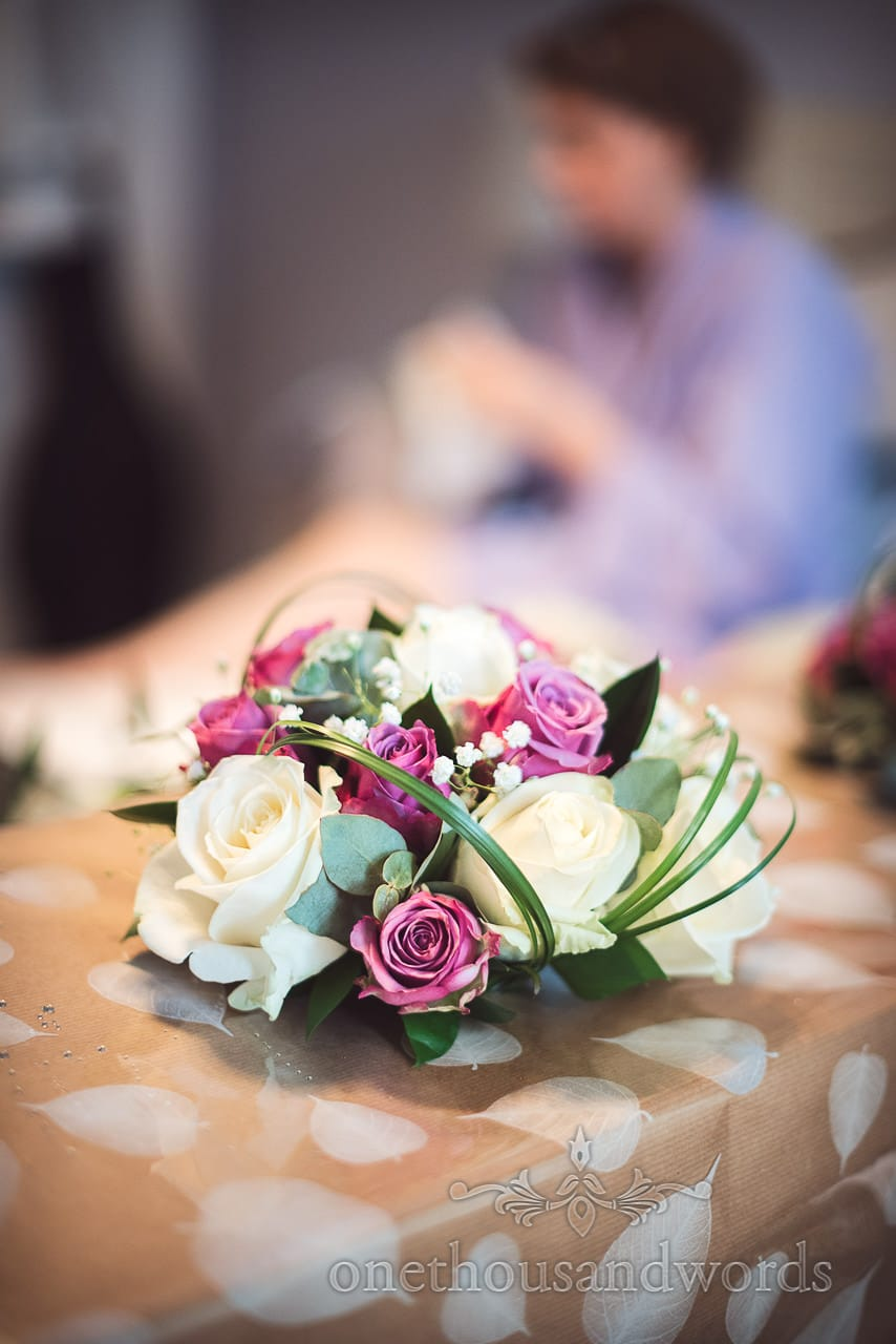 Close up photograph of White and purple wedding flower bouquets with green foliage