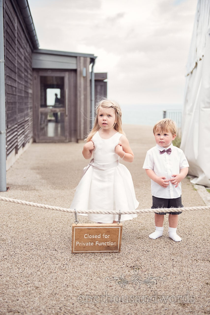 Cute flower girl and page boy next to closed sign at Durlston Castle Wedding