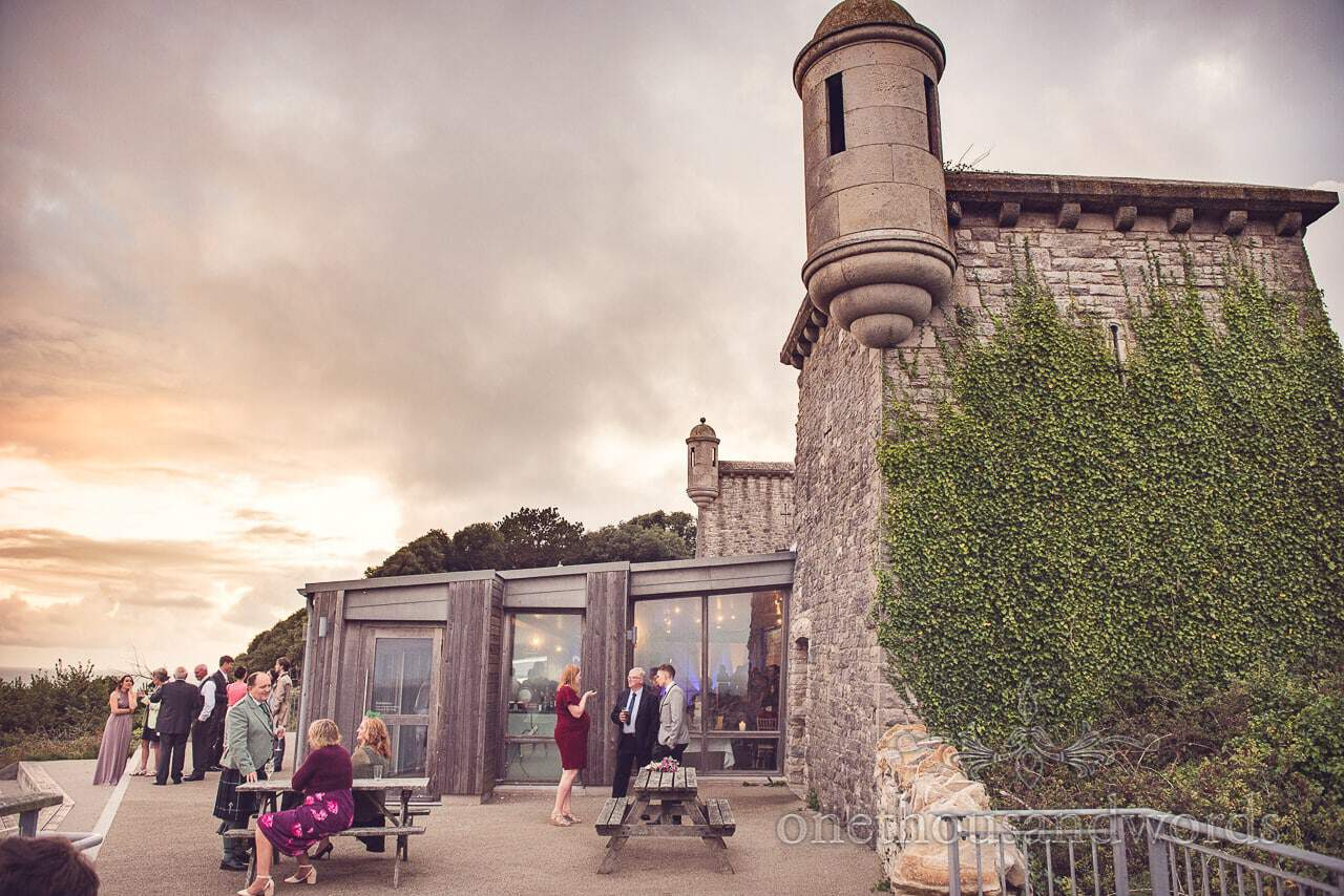 Durlston Castle Wedding Photograph of guests outdoors sunset wedding reception
