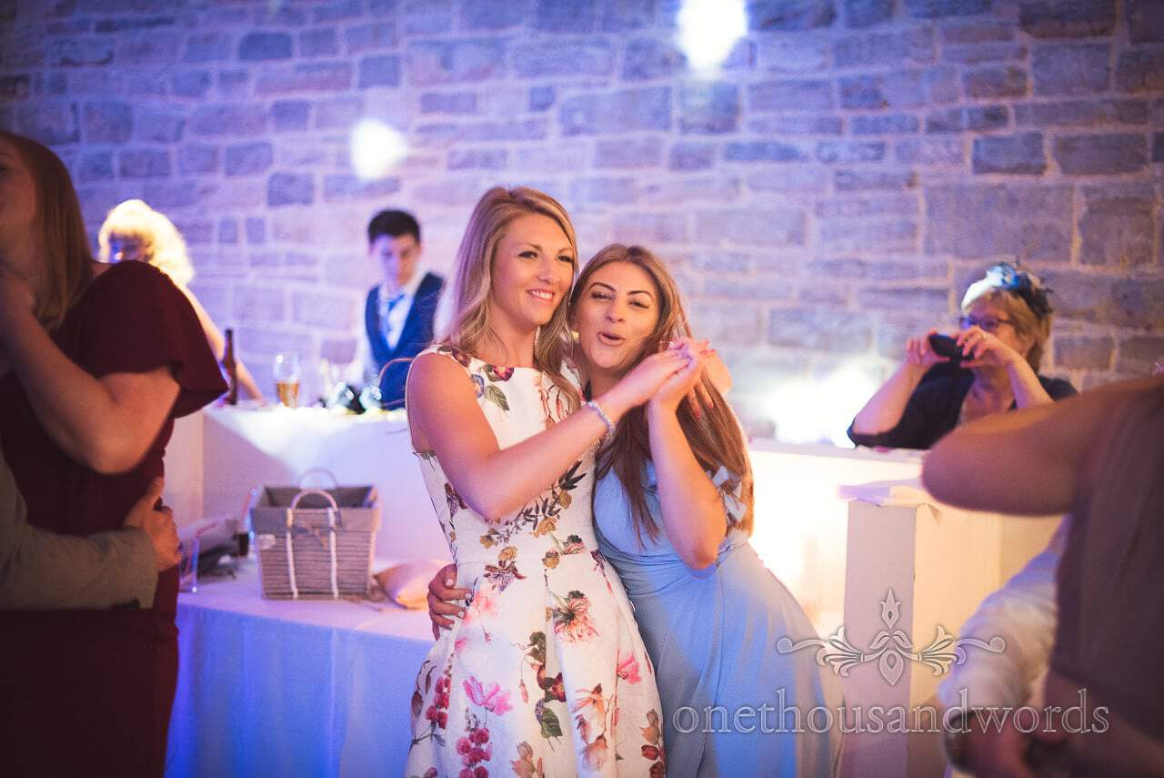 Durlston Castle Wedding Photographs of female wedding guests dancing together