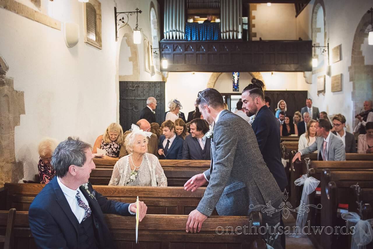 Elderly wedding guest talks to groomsmen in church before wedding ceremony
