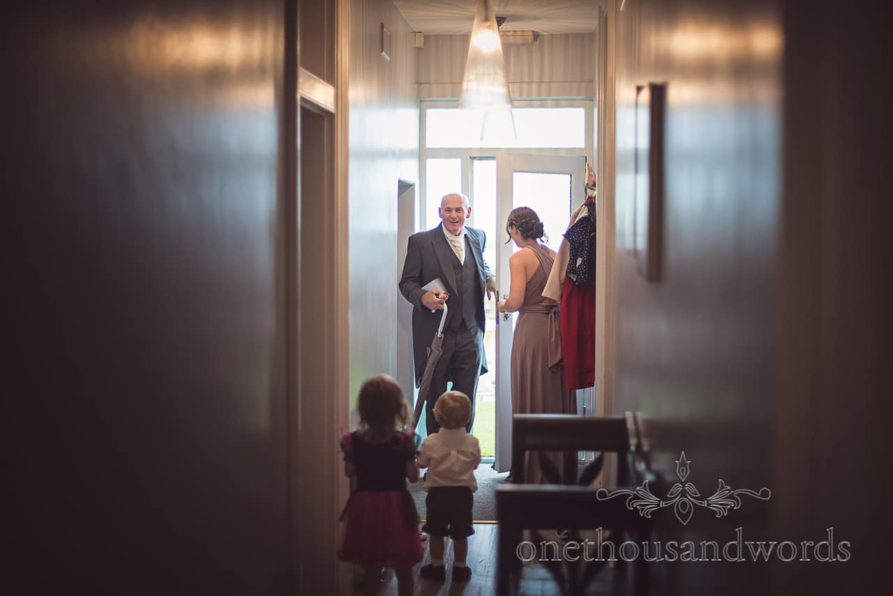 Father of bride in grey tail suit arrives during wedding morning preparations