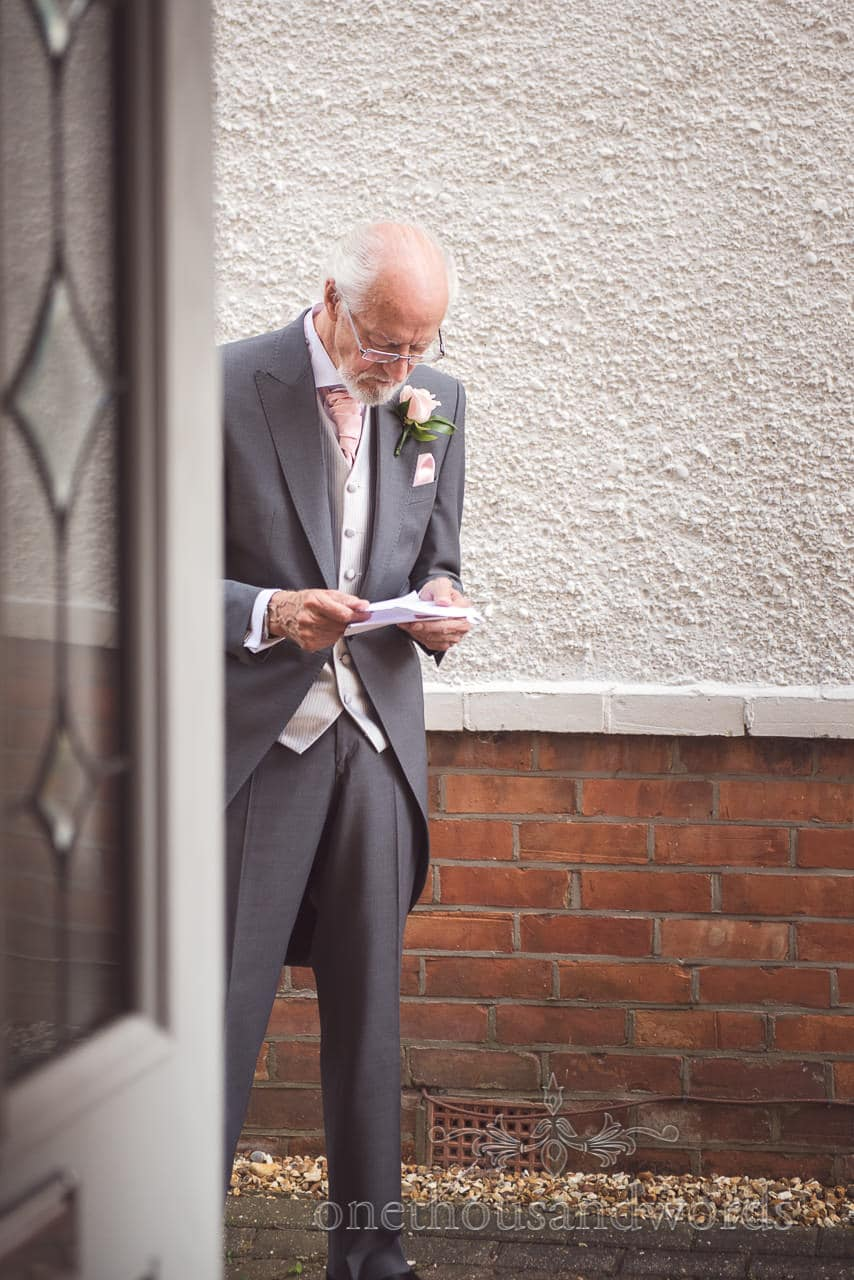 Father of the bride in grey tail suit practices wedding speech outside family home