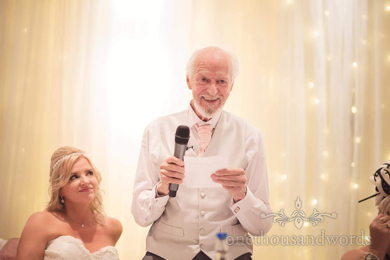 Father of the bride laughs during his wedding speech against LED backdrop