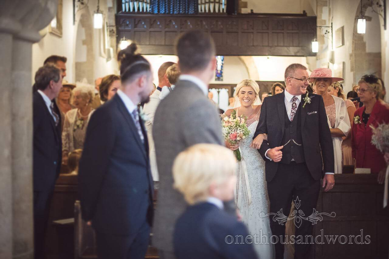 First look photograph of bride smiling at groom as she is walked up the aisle in Church