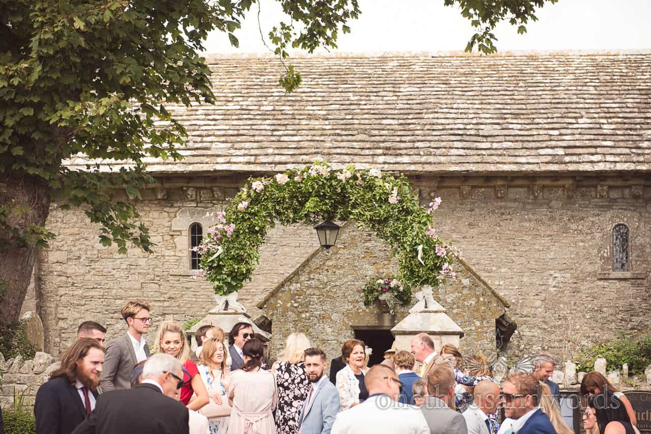 Flower and foliage archway with wedding guests outside stone church wedding venue