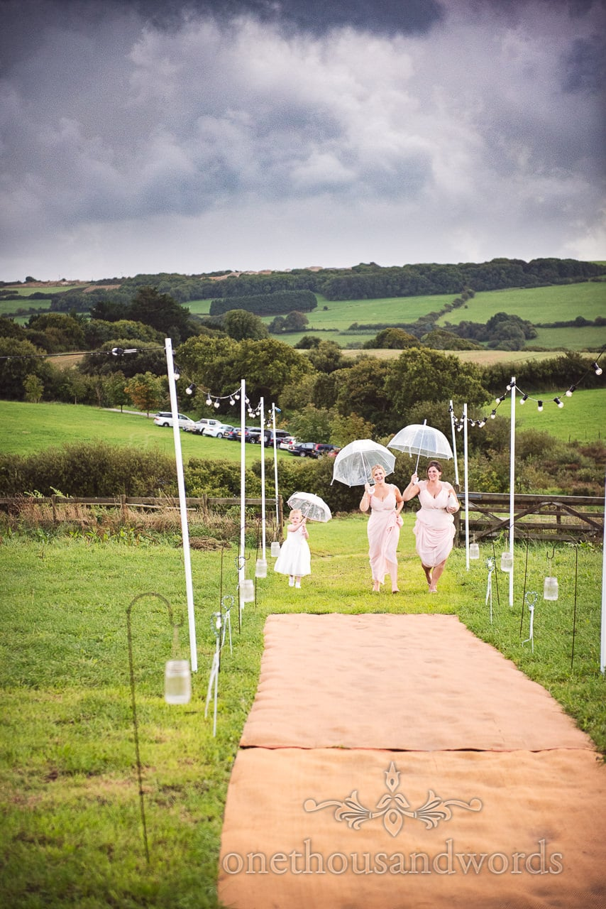 Flower girl and bridesmaids with umbrellas at Purbeck Valley Farm wedding photographs