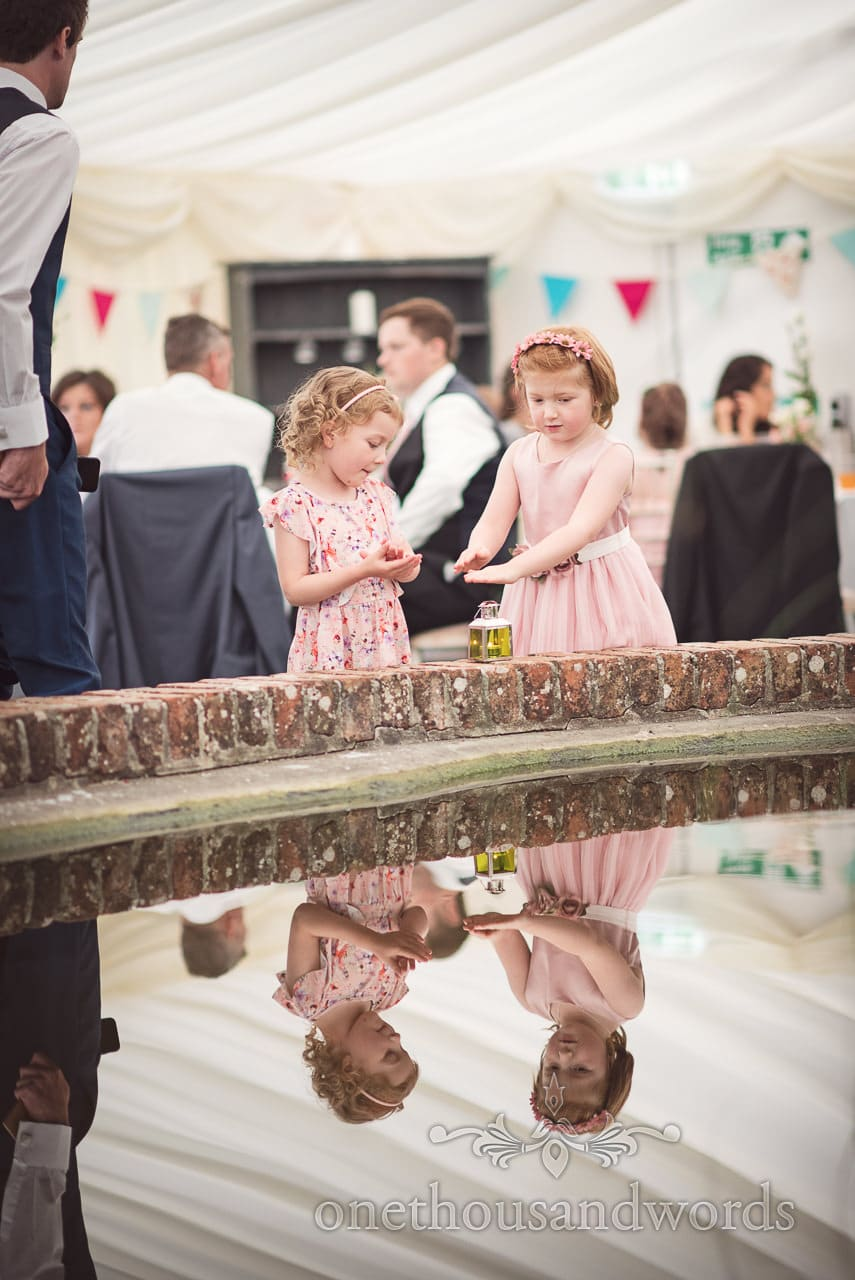 Flower girl and friend by pond in courtyard marquee at Coppleridge Inn Wedding Photographs