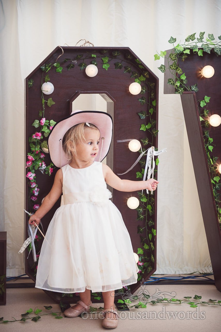 Flower girl in pink hat during reception at Purbeck Valley Farm wedding photographs