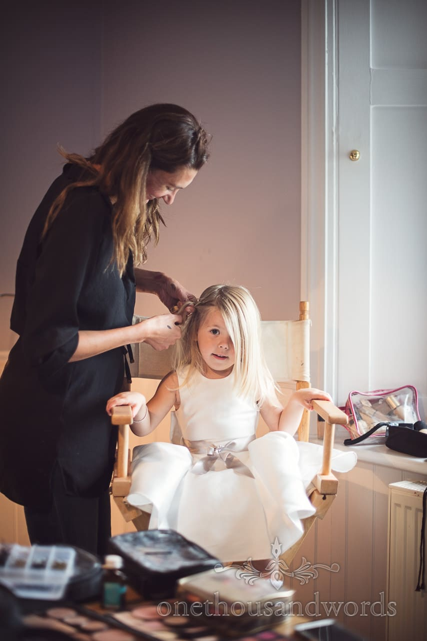 Flower girl in white dress with silk ribbon bow has wedding hair styled