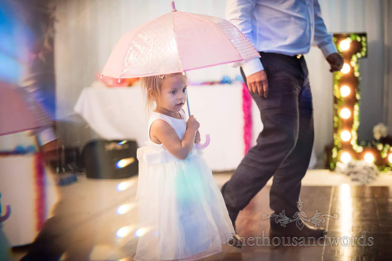 Flower girl with umbrella at Purbeck Valley Farm wedding photographs