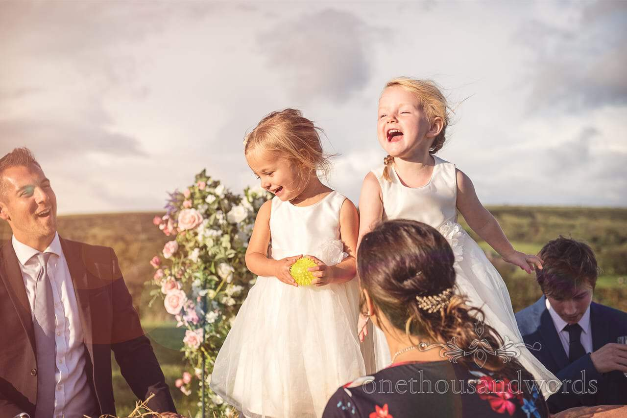 Flower girls play in the sunshine at Purbeck Valley Farm wedding photographs