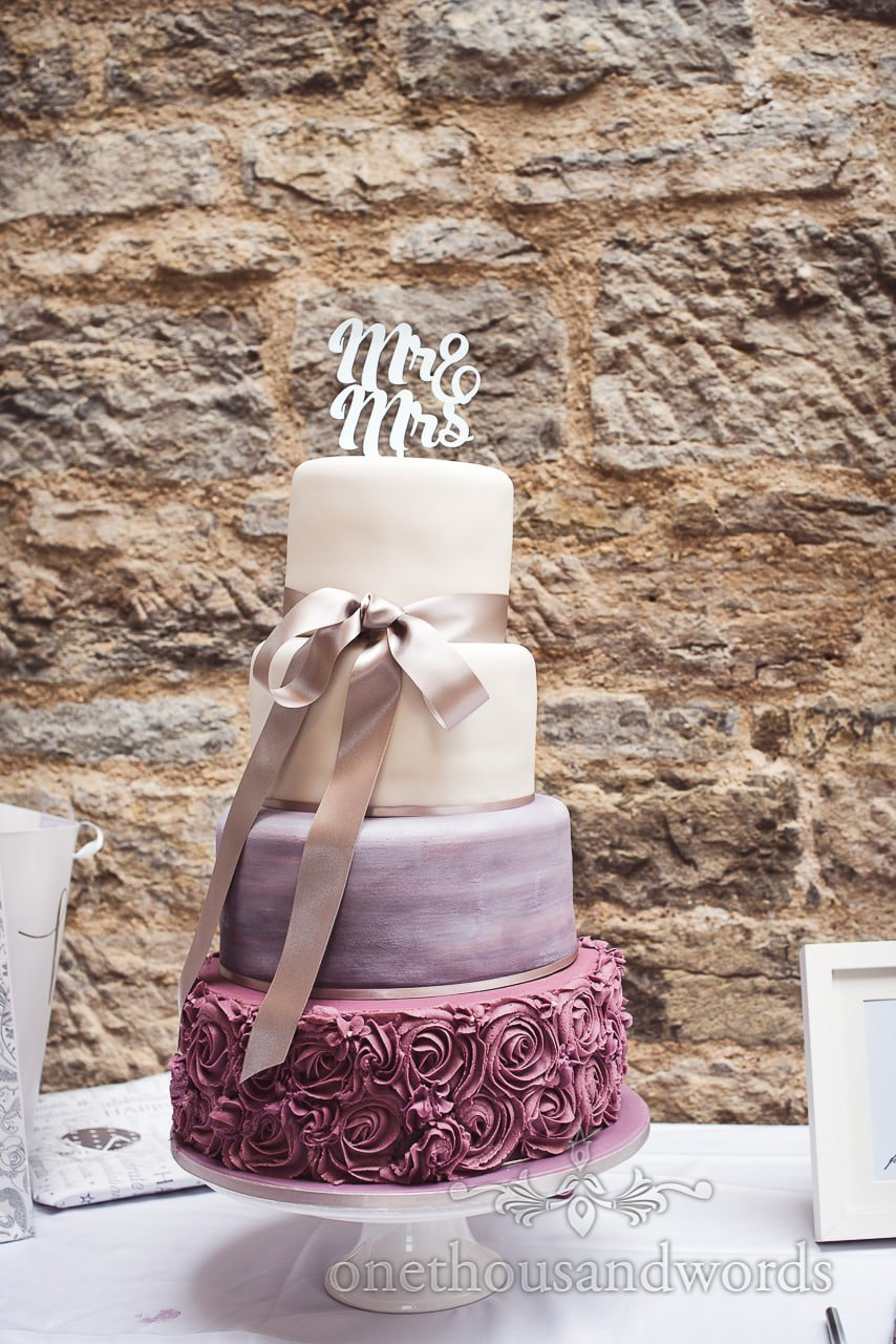 Four tier wedding cake with iced swirls, ribbon and Mr & Mrs sign against stole wall
