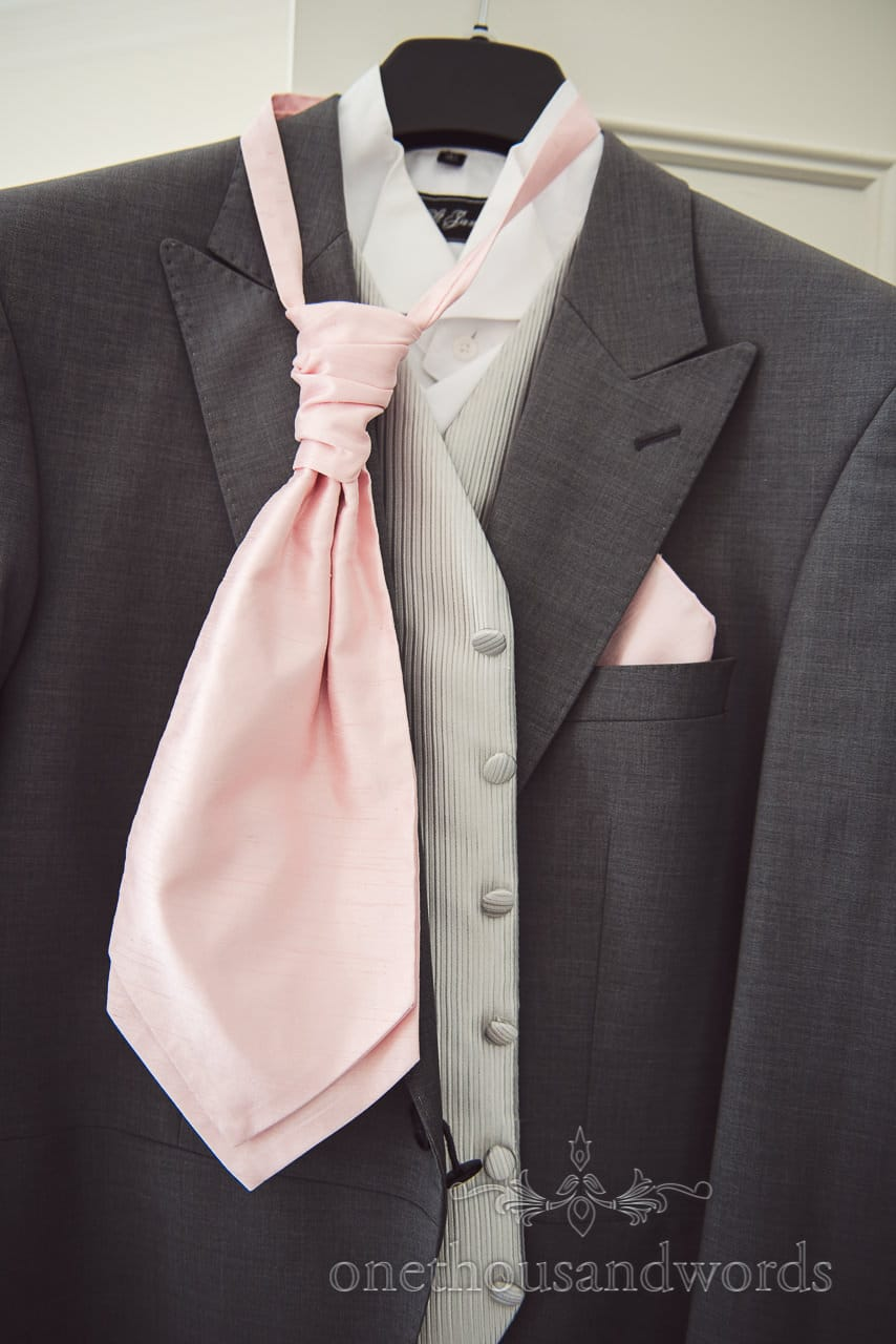 Gray wedding tail suit with silver waistcoat and pink cravat hanging on wedding morning