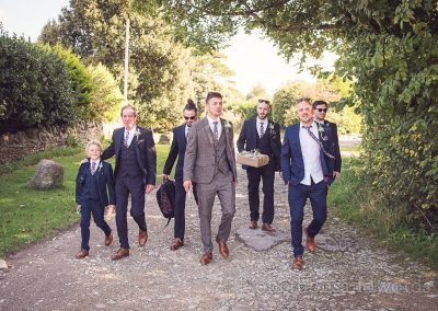 Gromsmen in suits looking cool walking down country lane on wedding morning
