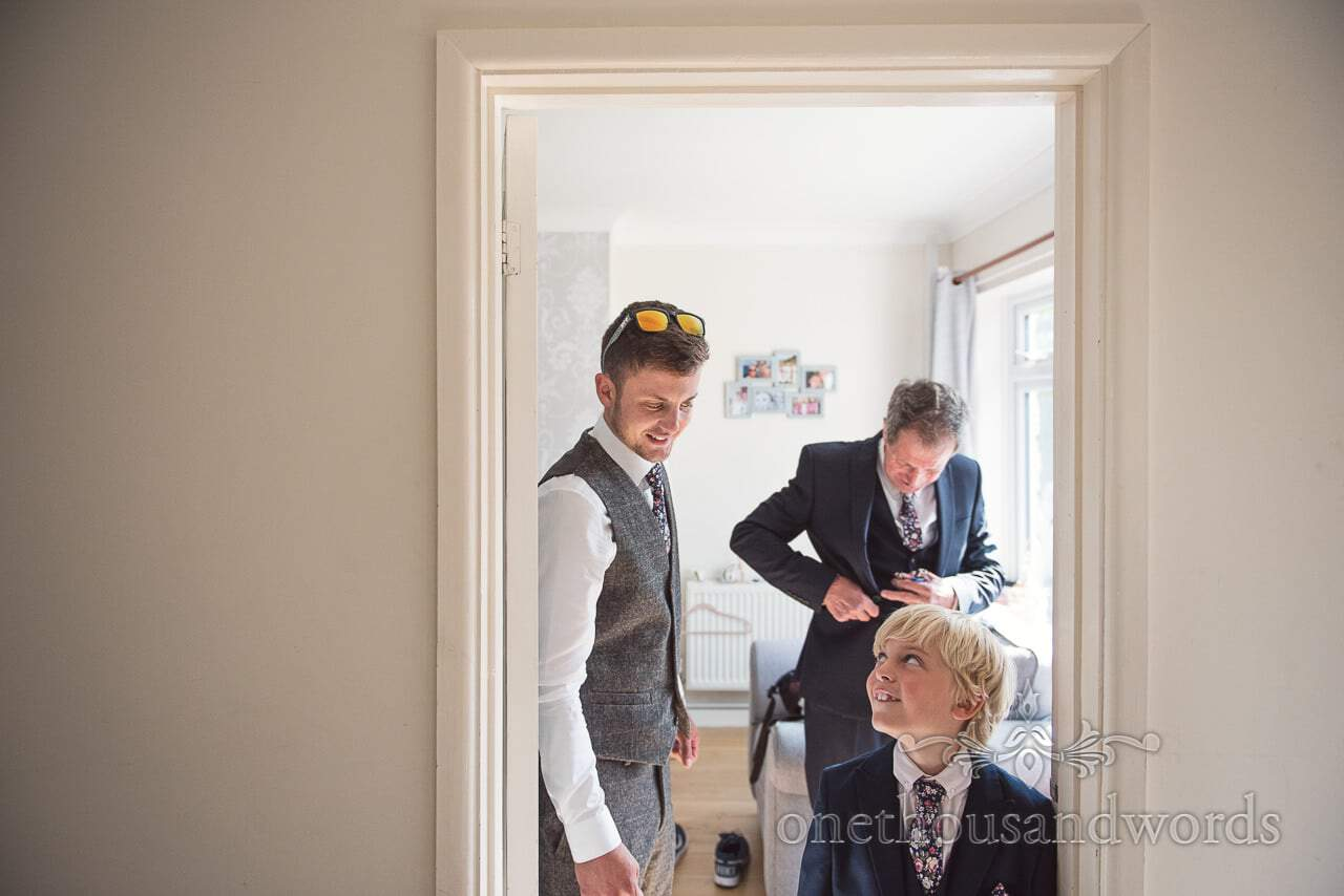 Groom and his son look at each other in wedding suits on wedding morning