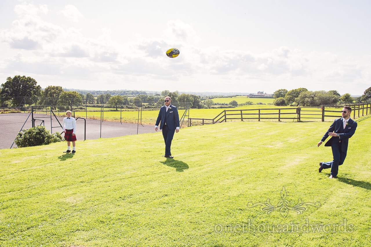 Groom ,Best man and guest play with rugby ball at Coppleridge Inn Wedding Photographs