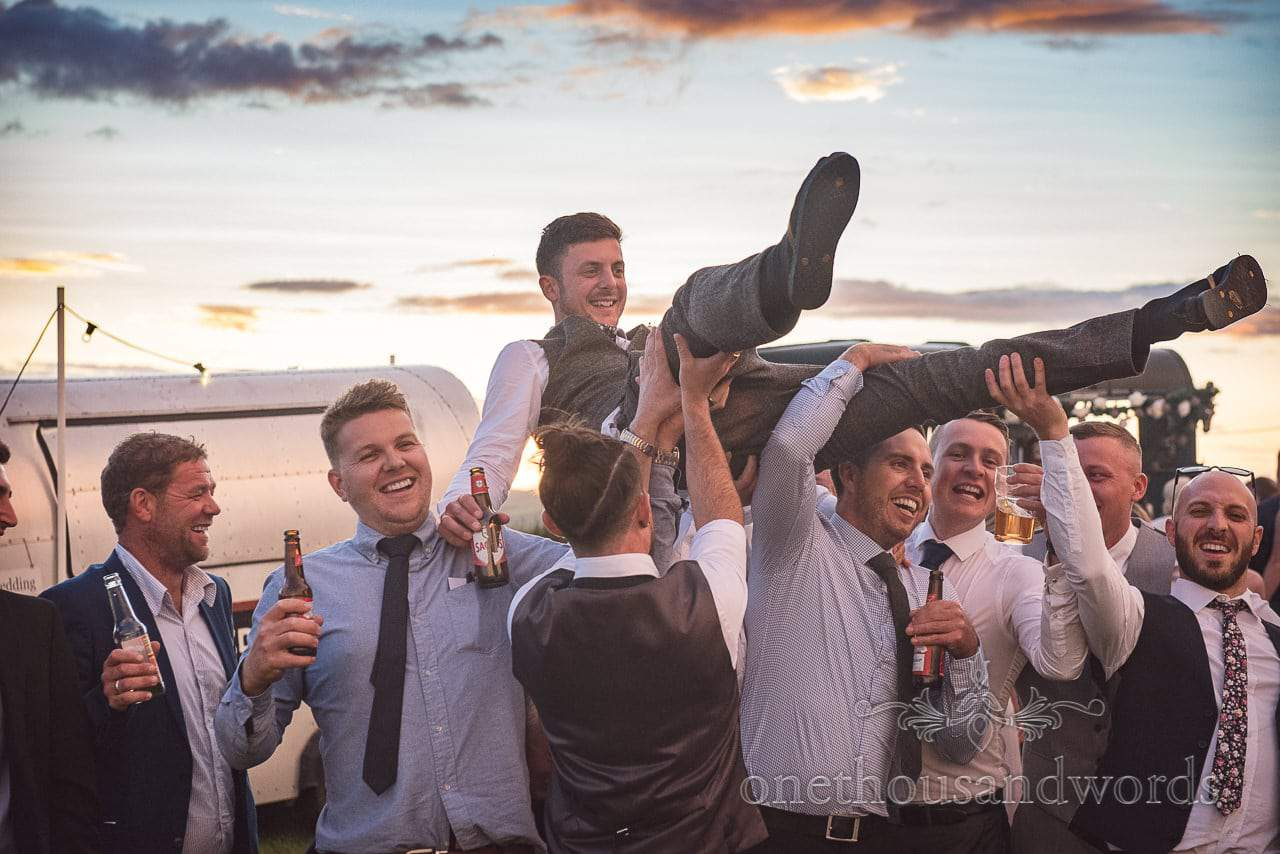 Groom gets thrown in the air by guests at Purbeck Valley Farm wedding photographs