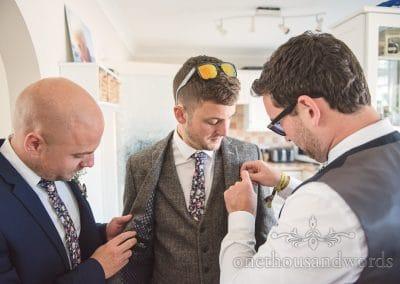 Groom has three piece wedding suit adjusted by groomsmen on wedding morning