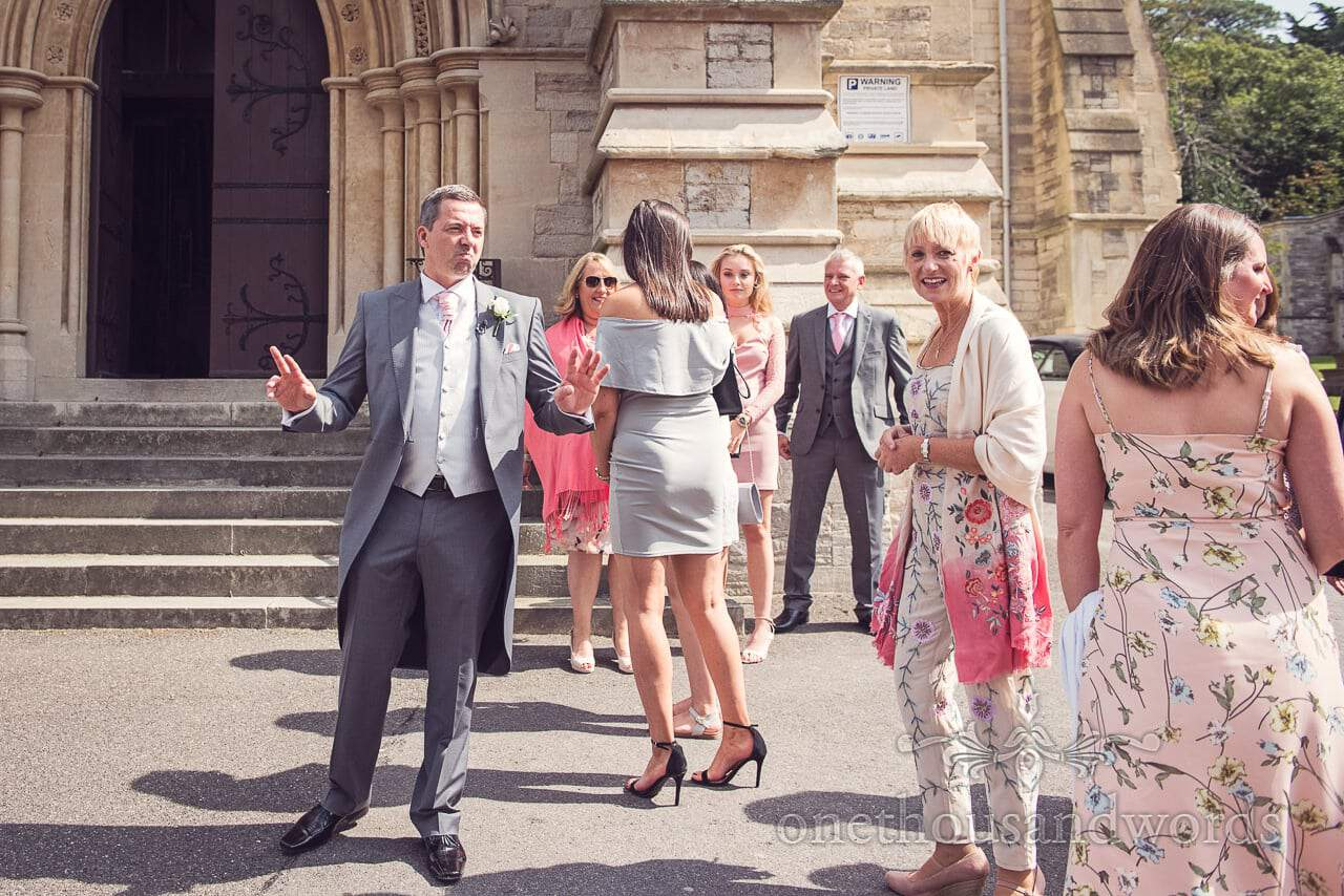 Groom in grey suit calms wedding guests down outside Bournemouth church wedding