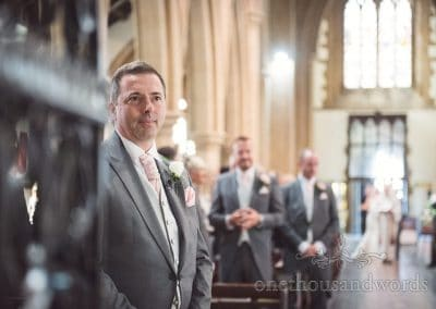 Groom in grey suit waits for bride to walk up aisle at St Peter's church wedding in Bournemouth