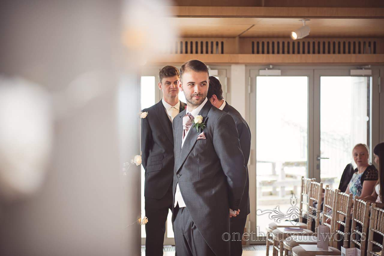 Groom in grey tails suit waits for bride at Durlston Castle Wedding ceremony